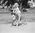 Blond kindje op een Mickey Mouse hobbelpaard in Suriname, Bestanddeelnr 252-6865.jpg