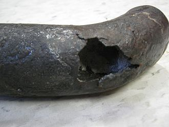 Caustic embrittlement - A tube damaged by caustic embrittlement. White caustic deposits can be seen inside.