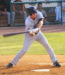 "A man in a gray baseball uniform emblazoned with blue letters reading ""CONNECTICUT"" swings a baseball bat right handed, checking his swing."