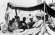 A number of men dressed in shorts and shirts with sleeves rolled up, one in a singlet sit in the shade of an awning. Several wear pith helmets, one of whom sits in the sun shirtless outside the awning leaning against a pole holding up the awning.