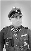 A man wearing a peaked cap with skull emblem, a military uniform with various military decorations and an Iron Cross displayed at the front of his uniform collar.
