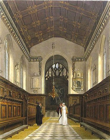 A chapel with a narrow chancel arch with memorials either side, black and white tiles on the floor, decorated wooden benches on each side of the aisle, and a painting in front of the main window. A man in dark academic or clerical robes talks to two women wearing bonnets and white dresses.