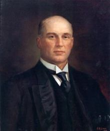 A painted portrait of an unsmiling bald white man in a three piece suit