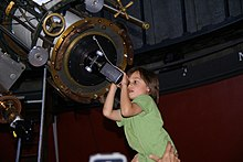 A little girl observing the solar eclipse at the Chamberlain observatory in Denver, Colorado