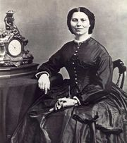 19th century photograph of a woman seated with her arm resting on a table. Her dark hair is neatly partedin the middle. She is smiling slightly