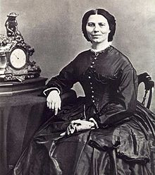 19th century photograph of a woman seated with her arm resting on a table. Her dark hair is neatly parted in the middle. She is smiling slightly