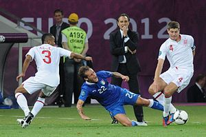 Tackle (football move) - Alessandro Diamanti (blue 22) slide tackles Steven Gerrard (white 4) at Euro 2012.