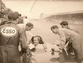 Colin Chapman - Chapman at the wheel of one of his own Lotus Eleven sports cars, during practice for the 1956 British Grand Prix Formula Two race at Silverstone Lotus Development Director Mike Costin on left holding notes. Chief Mechanic John Crosthwaite on right leaning on car.