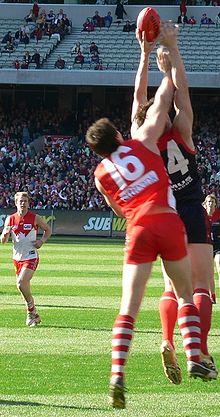Photo de deux joueurs de football australien en train de sauter pour attraper le ballon.
