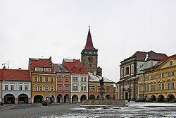 During winter, this town now has snow on the ground, and the sky is overcast (meaning it is completely covered by clouds).