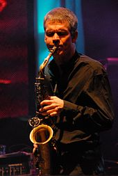A man with his eyes closed, wearing a black dress shirt and playing a saxophone