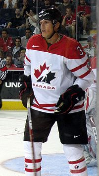 Hockey player in white Canada uniform. His hands are by his side, one holding his stick, and he stands near the sideline of the rink.