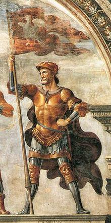 Détail d'un fresque montrant un soldat âgé, tenant fièrement un drapeau rouge avec un oiseau dessus, revêtant une armure et un casque de couleur dorés et argentés ainsi qu'une cape pourpre.