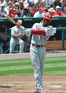 A dark-skinned young man wearing a red baseball helmet and a gray baseball jersey and pants with red trim swinging a baseball bat