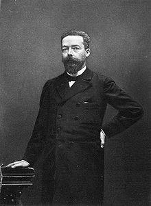 Fotografia em preto e branco de um homem barbudo, do pé.