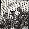 Drie Nederlandse officieren achter de muur van prikkeldraad van het concentratie, Bestanddeelnr 120-0464.jpg
