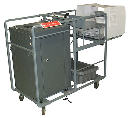 A cart holding an ES&S M100 ballot scanner and an AutoMARK assistive device, as used in Johnson County, Iowa, United States in 2010. ES&S M100 Automark cart.jpg