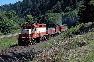 Central Oregon and Pacific Railroad - An EMD GP38-2 leads an NRHS excursion over the Coos Bay Line in 2005.