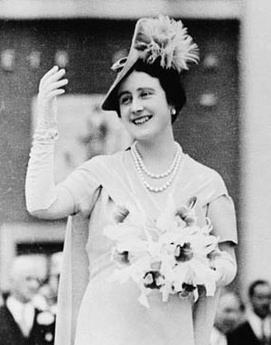 1930–45 in Western fashion - Queen Elizabeth wears long gloves with a short-sleeved dress and dramatic hat to visit the 1939 New York World's Fair.