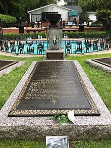 "A long, ground-level gravestone reads ""Elvis Aaron Presley"", followed by the singer's dates, the names of his parents and daughter, and several paragraphs of smaller text. In the background is a small round pool, with a low decorative metal fence and several fountains."