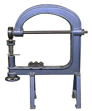 English wheel - An English wheel showing four interchangeable lower wheels (anvils), the larger fixed upper wheel, the pressure adjustment screw and a quick release mechanism