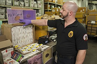 Counterfeit medications - US FDA official inspects package suspected of containing counterfeit drugs at an international mail facility in New York