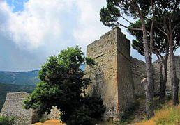 Imposantes fortifications en bon état avec muraille et tours dans un environnement méditerranéen (pins maritimes, herbes sèches).