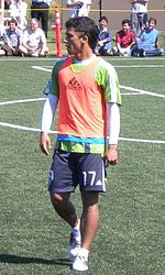 A man wearing a green T-shirt, orange bib and navy blue shorts, standing on a soccer field. In the background, people are sat watching him.
