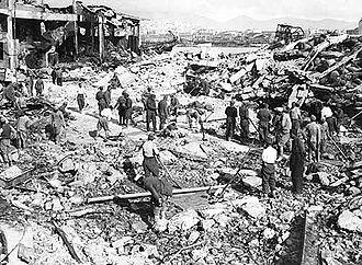 Hommes travaillant parmi des débris de bombardement, avec des restes de bâtiments sur la gauche.