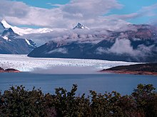 A glacier flows down to a bright blue lake surrounded by snow-capped mountains