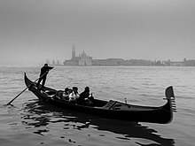 A black-and-white photo of what appears to be a cool, gray day. Four people, indistinct, sit in the middle of a long, thin boat, the gondola, moving to the right. High on the stern (left) stands a man with both hands on a long oar, which disappears into the water to his rear and slightly to his right. In the distant backgound, across the calm water, the buildings of Venice can be made out, standing in the mist.