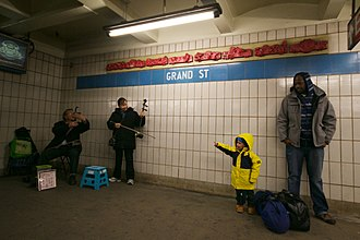 Grand Street (IND Sixth Avenue Line) - Musicians playing huqin for passengers in the station; behind them is the Trains of Thought frieze