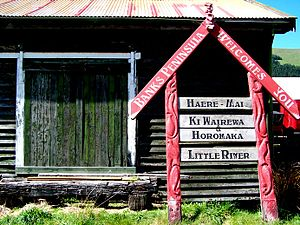 Little River, New Zealand - Welcome sign leaning against the goods shed of the former Little River Railway Station