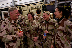 One man and three women in military fatigues converse while standing