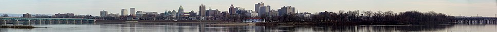 A panoramic of downtown Harrisburg from Wormleysburg, Pennsylvania, across the Susquehanna River from downtown. The view extends from the M. Harvey Taylor Memorial Bridge on the far left, across the cityscape including the Pennsylvania State Capitol and City Island, to the Walnut Street Bridge and the Market Street Bridge, as seen in March 2013.