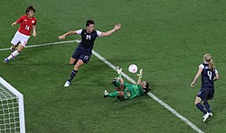 Soccer game between Japan and United States. Goalkeeper Hope Solo lies on the ground saving a ball, while Wambach is next to her.