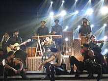 Madonna sitting onstage singing, surrounded by her dancers in a circle.