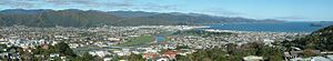 Lower Hutt - Lower Hutt from Normandale, in the western hills. On the right is the entrance to Wellington Harbour, with Matiu/Somes Island beneath. The Hutt River snakes from the right background to the left mid-ground, entering the harbour between the suburbs of Seaview and Petone. The Wainuiomata Hill Road climbs the hills in the centre background (the track in the middle of the left half of the background is a firebreak, not a road). At the foot of the Wainuiomata Hill Road is the Gracefield industrial area.