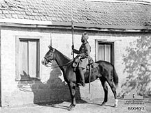 In a black and white photograph, a man wearing a turban and military uniform sits astride a stationary, dark-coloured horse, facing left. In his right hand he holds aloft a sword. Directly behind them stands a single-storey, brick building with two large windows and a tiled roof.