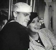 Cagney in a sailor suit with a smiling actress leaning on him. 2a61da735a4b
