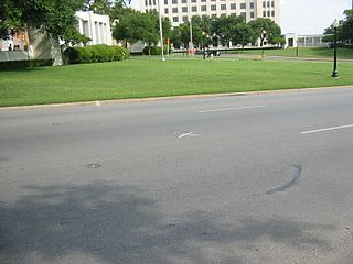 Elm Street vue de la pergola et de la butte herbeuse. Le X sur Elm Street marque l'endroit du tir mortel