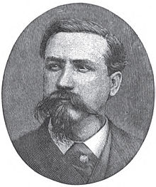 A man with dark hair and a dark, wiry mustache and goatee wearing a white shirt and black jacket