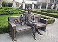 Pomnik - ławeczka profesora Józefa Kostrzewskiego w Ogrodzie Zamkowym obok Zamku Cesarskiego w Poznaniu. Fot. Wikimedia Commons, autor: MOs810, lic. CC-BY-SA-3.0.