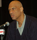 Bald headed black man speaking into a microphone. Headshot only with a polo shirt and sweater.