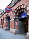 "A red-bricked building with a dark blue sign reading ""KING'S CROSS ST. PANCRAS"" in white letters and several entranceways all under a grey sky"