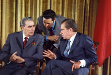 Two older men in suits sit next to each other, while a third stands behind leaning in to listen to the right man talk. US President Richard Nixon talked with Soviet leader Leonid Brezhnev in 1973.