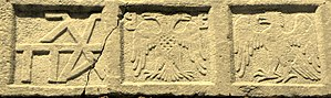 Byzantine flags and insignia - Relief at the Castle of Mytilene, showing the family cypher of the Palaiologoi (left), the Byzantine double-headed eagle (centre) with the Gattilusi coat of arms on its breast, and the eagle of the Doria family (right)