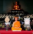 Luang Por Dhammajayo with honnorific fan, sitting in Ubosoth.jpg