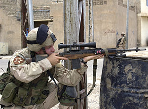 A sniper peers through the scope of his rifle ...