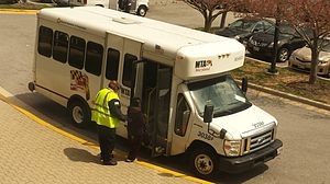 Paratransit - MTA Mobility vehicle operator assisting a customer board a paratransit vehicle